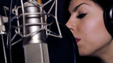 Young beautiful girl sings.Young singer singing into a microphone.Portrait close up of the singer.Recording studio.Recording in the studio singers. — Stock Video