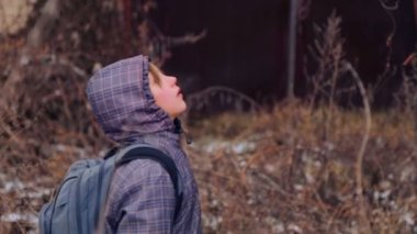 Caucasian boy explores the old agricultural machinery. Child teenager on an abandoned farm in the winter. The old farm. Rusted farm equipment. — Vídeo Stock