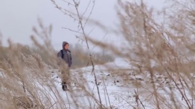 Caucasian boy teenager traveling in winter. The child goes on a winter road through the fields. Purposeful teenager overcomes the hard way. — Stockvideo