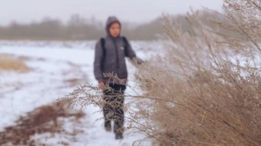 Caucasian boy teenager traveling in winter. The child goes on a winter road through the fields. Purposeful teenager overcomes the hard way. — 图库视频影像