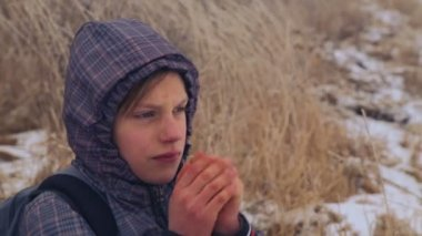 Caucasian boy teenager warm frozen hands. The child froze walking in nature in winter. Portrait of teenage boy closeup, warming his hands. — Stock Video