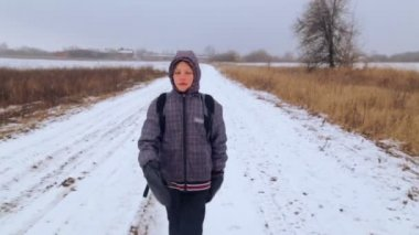 Caucasian boy teenager traveling in winter. The child goes on a winter road through the fields. Purposeful teenager overcomes the hard way. — Stock Video