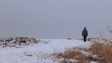 Caucasian boy teenager traveling in winter. The child goes on a winter road through the fields. Purposeful teenager overcomes the hard way. — Stok video