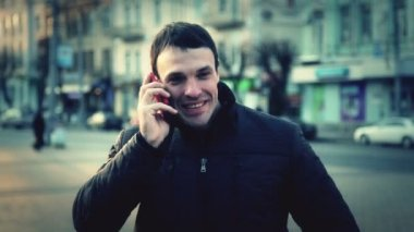 Portrait of a young man in the city. Caucasian guy talking on the phone in the city. Man tourist in another city. — Stock Video