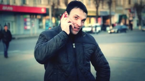 Portrait of a young man in the city. Caucasian guy talking on the phone in the city. Man tourist in another city. — Vidéo