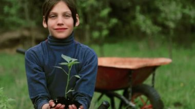 Caucasian boy on a bed in the garden.The child is engaged in spring planting. Boy teenager in nature near the bed. Boy with a seedling in her hands.Organic farming. — Stock Video
