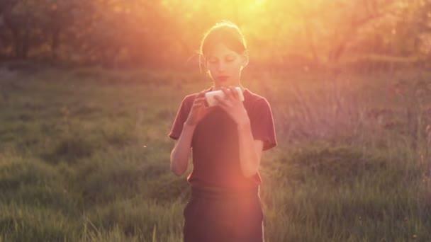 Muchacho caucásico con el teléfono en la naturaleza. Adolescente muchacho con un smartphone al atardecer. Muchacho con sunset fotografías de teléfono. Naturaleza, gente y tecnología. — Vídeo de stock