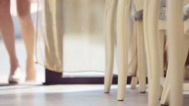Beautiful female legs in walking. Feet girl model sitting in a cafe. Female feet in shoes. Very beautiful female gait. — Стоковое видео
