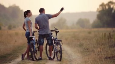 A young couple enjoying cycling in nature. Man and woman walking, biking. Young enamored couple walking in a field. Sport, recreation, lifestyle. — Stock Video