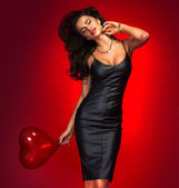 Lovely brunette woman with heart balloon. — Stock Photo