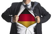 German flag with businessman showing a superhero suit underneath — Stock Photo