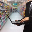 Person Typing on a modern laptop in supermarket in blurry — Stock Photo #75792097