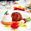 Dessert plate on restaurant table ready. Chocolate ice cream, fruit and biscuits. romantic restaurant table — Stock Photo #68719157