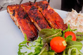 Ribs with some salad and coleslaw in the corner — Stock Photo