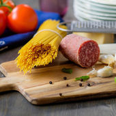 Dried spaghetti pasta with some salami on the side and tomatoes  — Stock Photo
