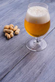 Beer with foam and peanuts on the side — Stock Photo
