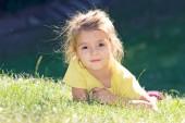 Little girl lying on the green grass.Child outdoor closeup face  — ストック写真