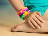 Loom bracelets on child hand close up.Rubber colorful wrist acce — Stock Photo