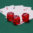Winning poker hand of four aces playing cards and red dice on green background — Stock Photo #60475379