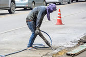 Road repairing works with jackhammer — Stock Photo