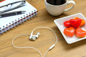 Office table with notebook, headphone and coffee cup. — Stock Photo