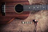 Close up of ukulele and earphone on old wood background — Stock Photo