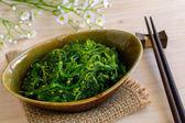 Traditional Japanese seaweed salad with chopsticks — Stock Photo