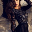 Beautiful girl with dark hair in black lace dress — Stock Photo