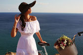 Beautiful girl with dark hair in elegant dress and hat with bicycle — Stock Photo
