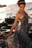 Beautiful girl with dark hair in elegant silk dress posing on beach — Stock Photo