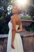 Beautiful bride in elegant dress posing in sunlight rays  — Stock Photo