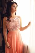 Beautiful woman with dark hair in elegant coral dress with diadem — Stock Photo