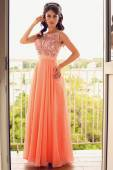 Beautiful woman with dark hair in coral dress posing on balcony — Stock Photo