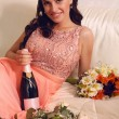 Beautiful bride in elegant coral dress holding bottle of champag — Stock Photo #52806389