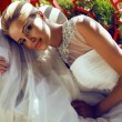Beautiful bride with blond hair in wedding dress lying on sofa — Stock Photo #52806485
