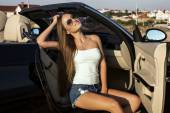 Sexy girl with long hair posing in luxury cabriolet — Stock Photo