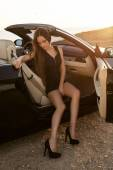 Sexy girl with dark hair in elegant dress posing in cabriolet — Stock Photo