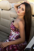 Sexy girl with long dark hair posing in cabriolet — Stock Photo