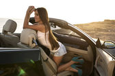 Sexy girl with dark hair posing in luxury cabriolet — Stock Photo
