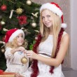 Cute little girl with her beautiful mother in Santa's hat — Stock Photo #53476183