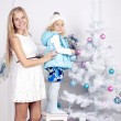 Cute little girl with her mom decorating Christmas tree — Zdjęcie stockowe #53476185