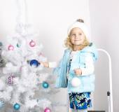 Adorable little girl decorating Christmas tree — Stock Photo