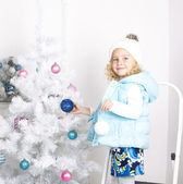 Funny little girl is decorating Christmas tree — Stock Photo