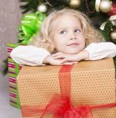 Mignonne petite fille tenant une boîte-cadeau et assis près d'un arbre de Noël — Photo