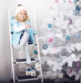 Smiling cute girl posing beside a decorated Christmas tree — Stock Photo
