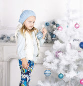 Beautiful little girl decorating Christmas tree — Stock Photo