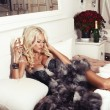 Sexy blond woman in lingerie and fur coat lying on bed with champagne — Stock Photo #53763701