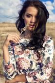 Portrait of beautiful woman with dark hair posing at summer field — ストック写真