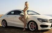 Sexy woman with blond hair posing beside a luxury auto — Foto de Stock