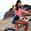 Pretty girl with dark hair in sport clothes sitting on bicycle — Stock Photo #55867617